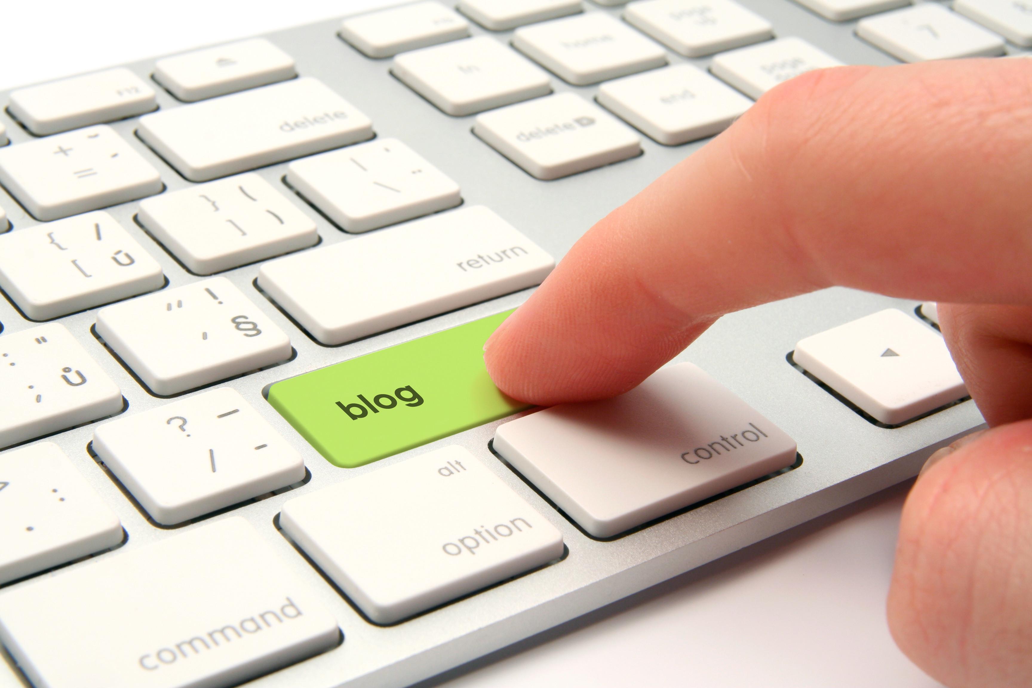 doigt cliquant sur un clavier où il est écrit blogue